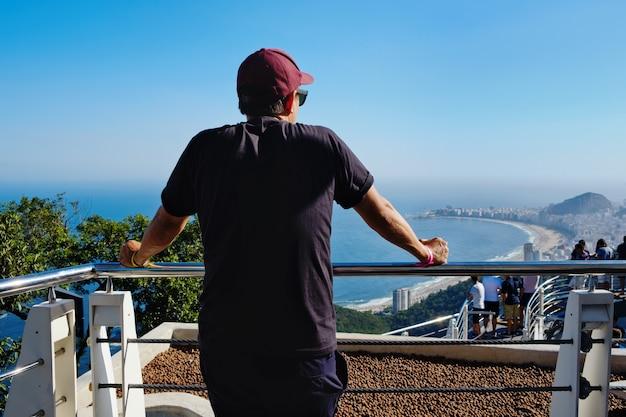 Turista a rio sul pan di zucchero guardando il rio de janeiro. brasile
