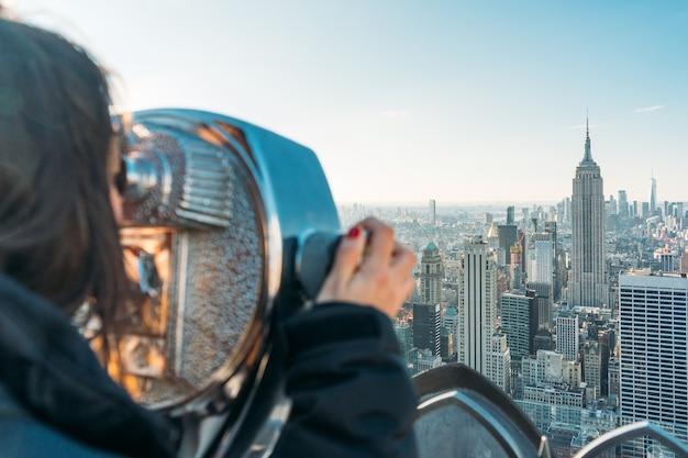 Turista che vede i grandi edifici di new york city attraverso un telescopio in una giornata di sole - primo piano