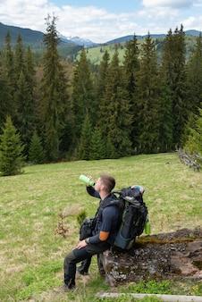Il turista si siede su un ceppo e beve l'acqua da una bottiglia