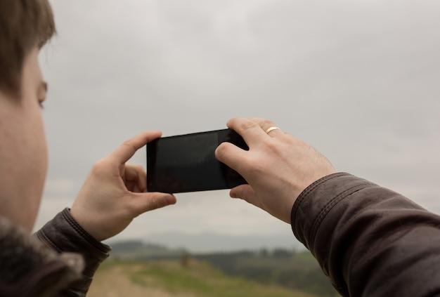 Turista che cattura foto della foresta e delle montagne sul telefono cellulare durante la sua vacanza. primo piano