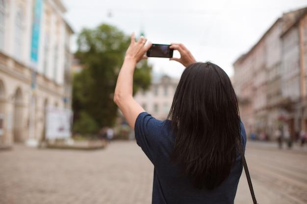 Turista che prende foto sullo smartphone nel centro urbano di lviv