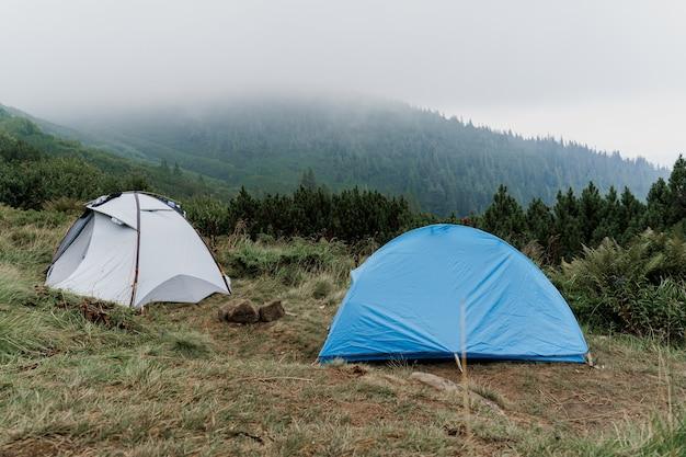 Tende turistiche sullo sfondo dei carpazi in una giornata piovosa e nebbiosa