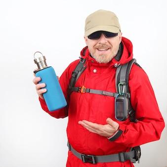 Il viaggiatore turistico in una giacca rossa mostra una bottiglia di metallo per l'acqua su uno spazio bianco