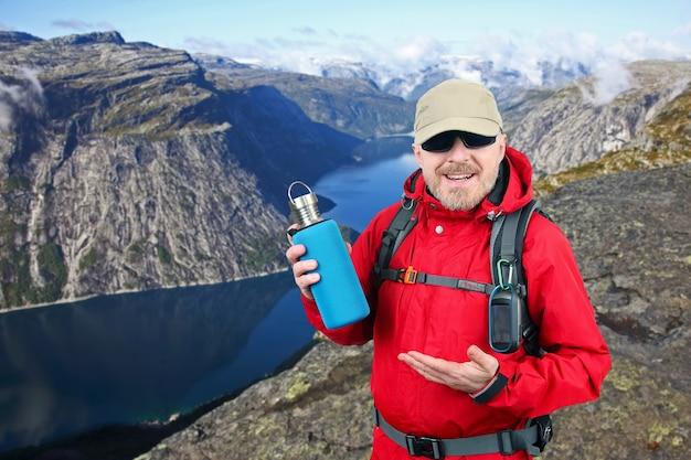 Il viaggiatore turistico in una giacca rossa mostra una bottiglia di metallo per l'acqua