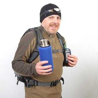 Il viaggiatore turistico mostra una bottiglia di metallo per l'acqua su uno sfondo bianco