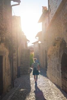 Turista che cammina nei dettagli del villaggio medievale di santo stefano di sessanio, edifici storici in pietra, vicolo antico, architettura in pietra della città vecchia. abruzzo, italia.