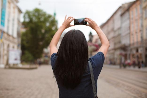 Turista che cammina attraverso il centro della città di lvov e scatta foto con il suo cellulare