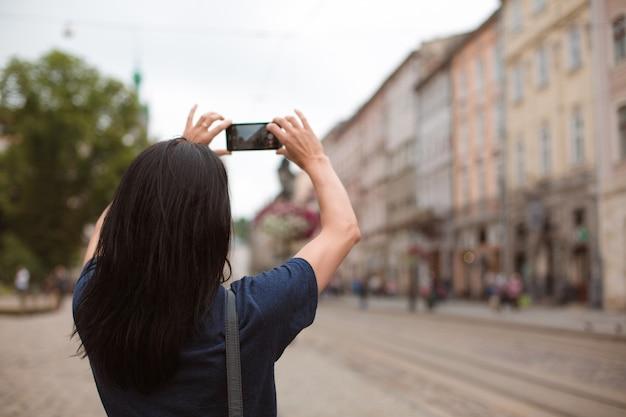Turista che passeggia per il centro della città e scatta foto con il suo cellulare. spazio per il testo