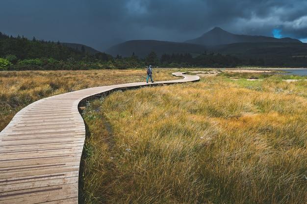 Turista che cammina sul percorso di legno. irlanda.