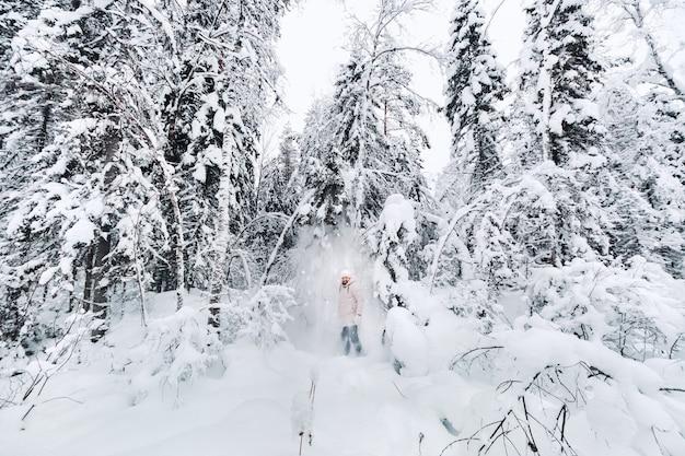 Un turista cammina in una foresta innevata. foresta invernale in estonia. viaggio attraverso la foresta invernale.