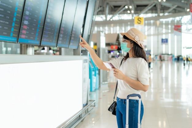 Turista che indossa la maschera per il viso controllo volo dalla scheda di partenza di arrivo
