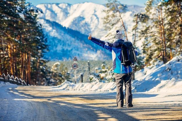 Il turista in inverno in montagna, in piedi sull'autostrada, ha voltato le spalle e prende la macchina