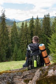 Il turista con uno zaino dietro di lui si siede appoggiato su un tronco in una radura di fronte alla foresta
