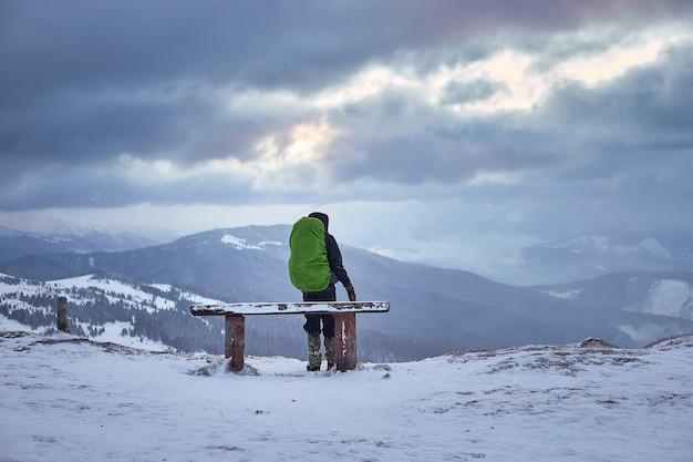 Turista con uno zaino e panorama montano. paesaggio invernale. escursionismo