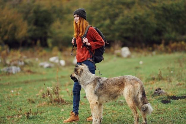 Turista con uno zaino cammina il cane nel campo viaggi montagne natura