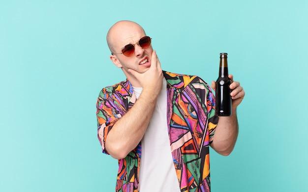 Turista con birra uomo turistico con la bocca e gli occhi spalancati e la mano sul mento, sentendosi spiacevolmente scioccato, dicendo cosa o wow
