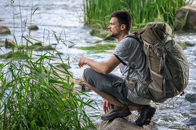 Un turista con un grande zaino da trekking vicino a un fiume di montagna nella calura estiva.