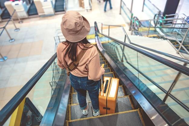 Turista con i bagagli giù per le scale mobili in aeroporto.