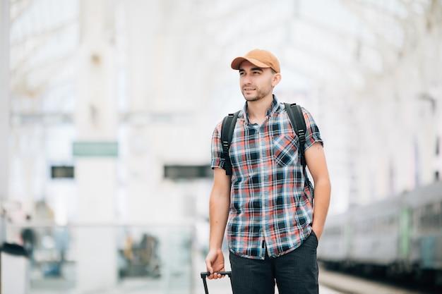 Turista con valigia per viaggiare alla stazione dei treni