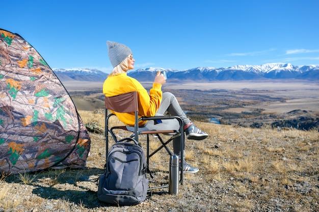 La donna turistica beve una bevanda calda da una tazza e gode del paesaggio in montagna