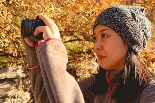 La donna turistica sta scattando una foto con la sua fotocamera mirrorless.