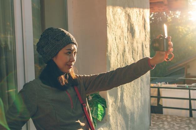 La donna turistica sta scattando una foto di selfie con la sua fotocamera mirrorless.