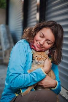 Donna turistica che gioca con il gatto senza tetto rosso