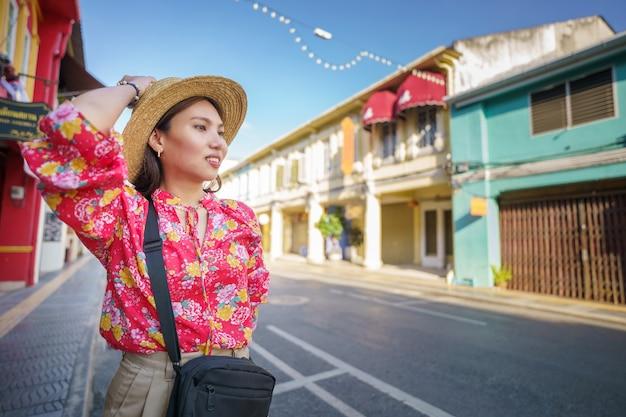 Donna turistica sulla strada città vecchia di phuket con la costruzione di architettura sino portoghese a phuket old town area phuket, thailandia.