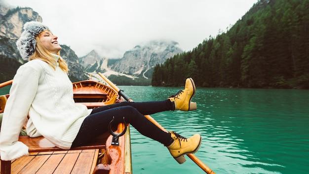 Donna turistica in barca a remi in legno tradizionale sul lago di braies alpino italiano