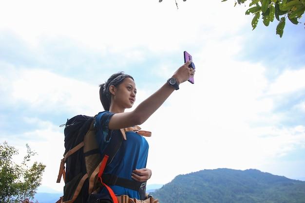 Una donna turistica utilizza uno smartphone in montagna