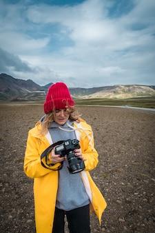 Donna turistica con la macchina fotografica in piedi vicino al bellissimo paesaggio islanda