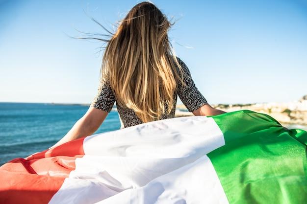 Una donna turistica con bandiera italiana che guarda il mare. tifoso di calcio italiano