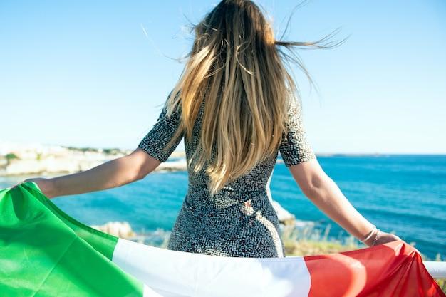 Una donna turistica con bandiera italiana che guarda il mare. tifoso italiano