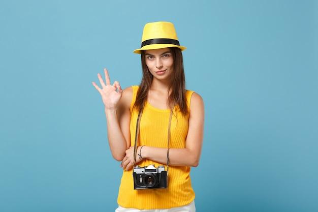 Donna turistica in abiti casual estivi gialli e cappello con macchina fotografica su blu