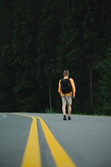 Turista in felpa gialla che cammina lungo la strada asfaltata al bosco di abeti di montagna