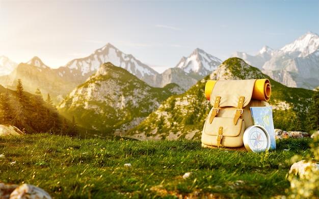 Zaino turistico con mappa e bussola sul campo in erba in montagna in giornata estiva