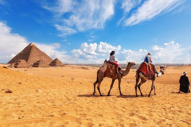 Turisti, cammelli, beduini e le piramidi nel deserto di giza.