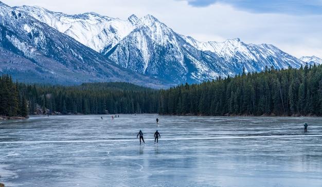 I turisti che fanno pattinaggio sul ghiaccio nel lago johnson superficie di acqua congelata in inverno il parco nazionale di banff