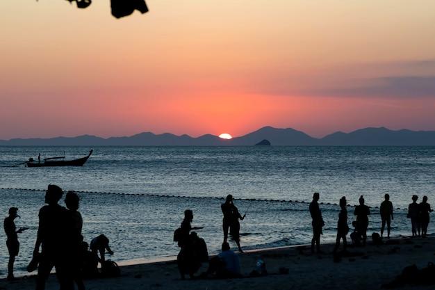 I turisti si godono il magnifico sole al tramonto che tramonta sulle montagne spiaggia sabbiosa tropicale