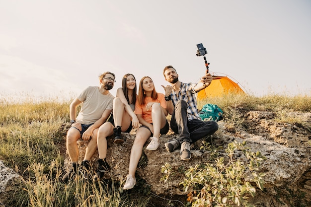 Turisti che riprendono vlog seduto su una scogliera in montagna.