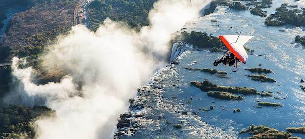 I turisti sorvolano le cascate vittoria sui trike. africa. zambia. le cascate victoria.