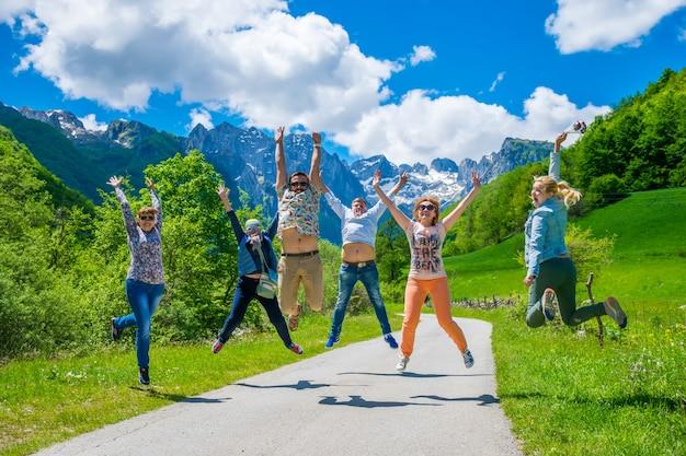 I turisti saltano con gioia sullo sfondo delle montagne innevate.