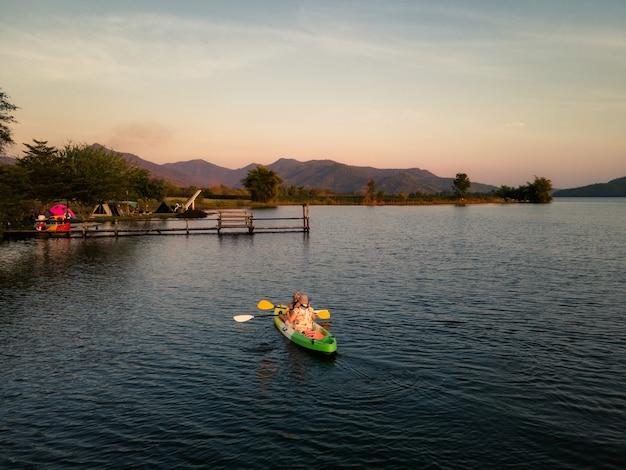 Turisti che remano in canoa sul lago e tramonto sulla vista sulle montagne