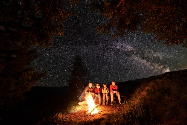 I turisti si siedono su un tronco accanto al fuoco con una grande fiamma sotto gli abeti sullo sfondo del cielo straordinario disseminato di stelle e sagome di montagne e colline