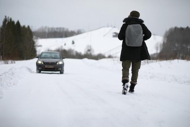 I turisti viaggiano attraverso il paese innevato. lungo la strada, cammina e fai l'autostop.