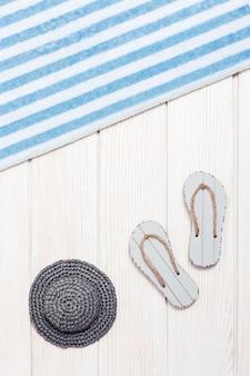 Asciugamano e ciabattine da spiaggia, cappello da sole su legno bianco, sfondo estivo. vacanze in mare.