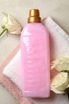 Asciugamano, liquido per bucato e rose su texture beige chiaro