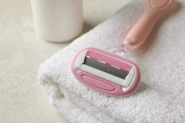 Asciugamano, rasoio e spray sul tavolo testurizzato