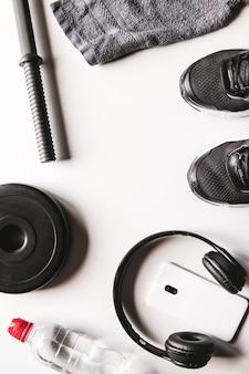 Asciugamano, scarpe da ginnastica, acqua e smartphone con le cuffie su sfondo bianco