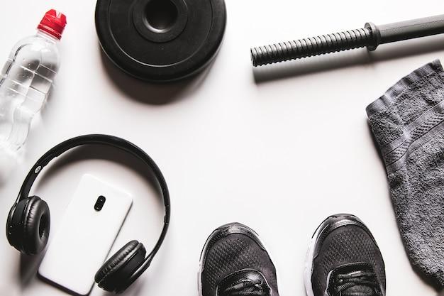 Asciugamano, scarpe da ginnastica, acqua e smartphone con le cuffie su un bianco